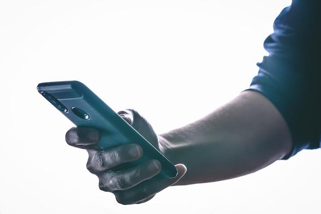 Mani che tengono e che mandano un sms in uno smartphone con luce posteriore e lo spazio della copia
