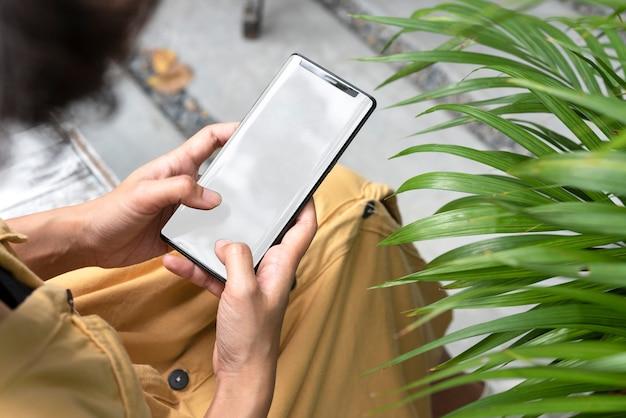 Mani che tengono e che utilizzano telefono cellulare con lo schermo in bianco in giardino.