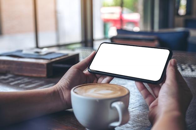 Mani che tengono e utilizzando un telefono cellulare nero con schermo vuoto orizzontalmente per guardare con una tazza di caffè sul tavolo di legno