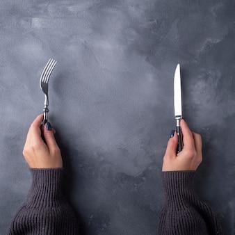 Mani che tengono forcella e coltello su superficie grigia. vista dall'alto