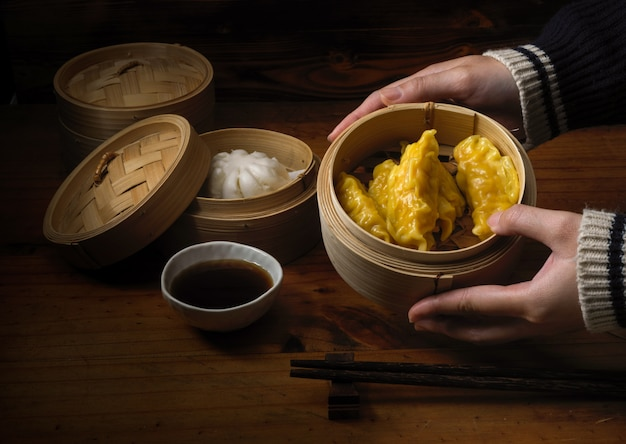 Mani che tengono gli gnocchi cotti a vapore che servono sulla cucitrice di bambù in ristoranti cinesi