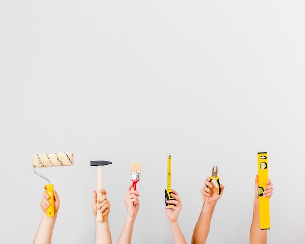 Mani che tengono gli strumenti della costruzione con lo spazio della copia