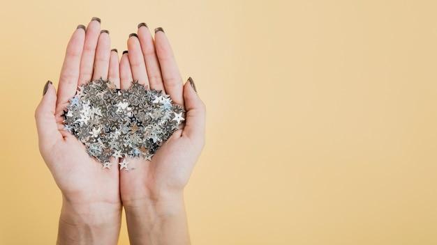 Mani che tengono glitter con copia spazio piatto disteso