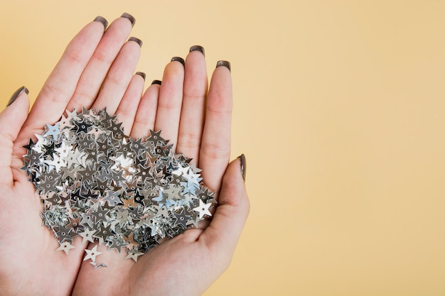 Mani che tengono glitter con copia spazio vista dall'alto