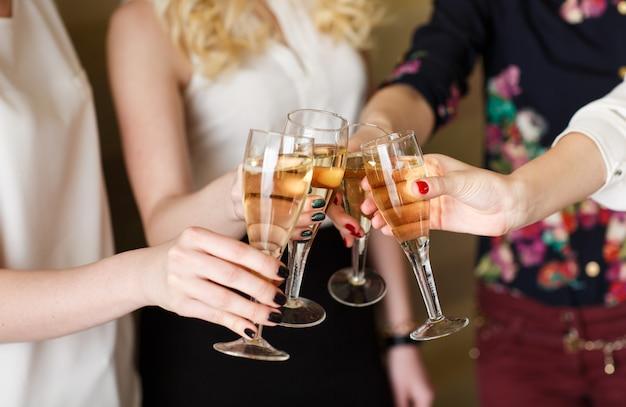 Mani che tengono i bicchieri di champagne facendo un brindisi