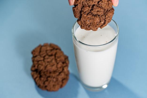 Mani che tengono i biscotti e le spezie del caffè su superficie rustica di legno. elegante posa piatta invernale.