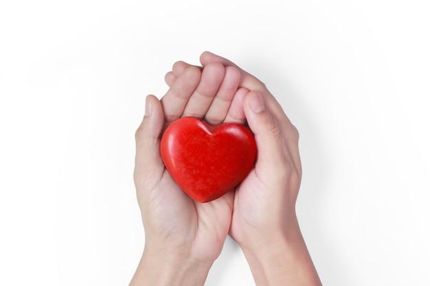 Mani che tengono i concetti di cuore rosso, salute del cuore e donazione