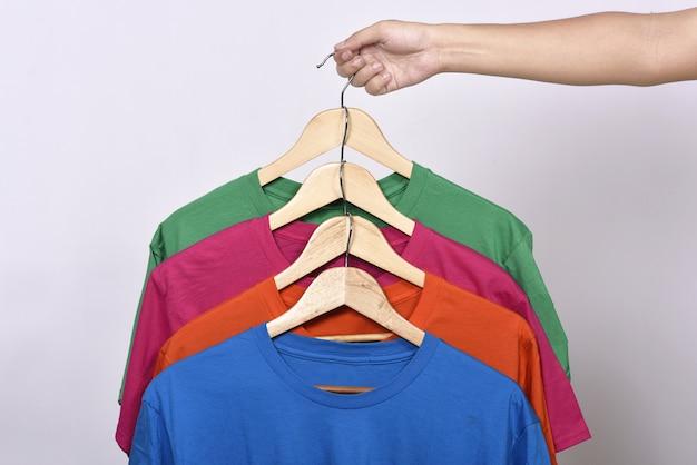 Mani che tengono i ganci appendiabiti con vestiti colorati