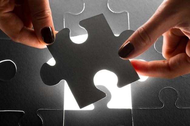 Mani che tengono i pezzi di puzzle, concetto di affari