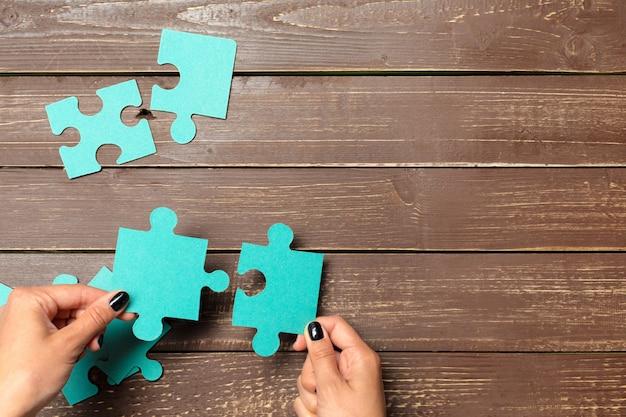 Mani che tengono i pezzi di puzzle, priorità bassa di concetto di affari