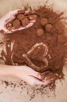 Mani che tengono i tartufi al cioccolato con la polvere di cacao