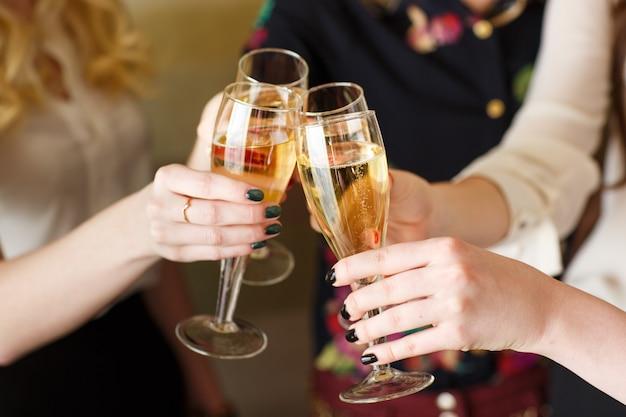 Mani che tengono i vetri di champagne che producono un brindisi