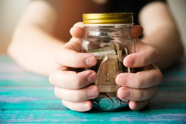 Mani che tengono il barattolo di risparmio
