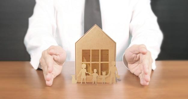 Mani che tengono il bene immobile del riparo dell'alloggio senza tetto della casa, concetto di assicurazione della casa della famiglia