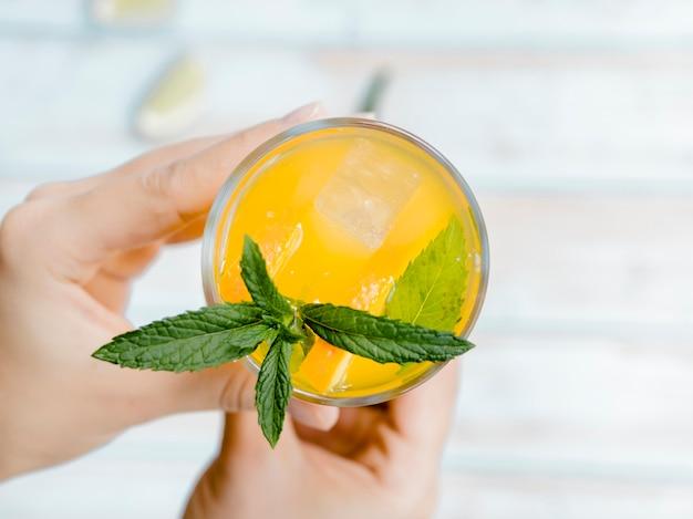 Mani che tengono il bicchiere di succo d'arancia ghiacciato