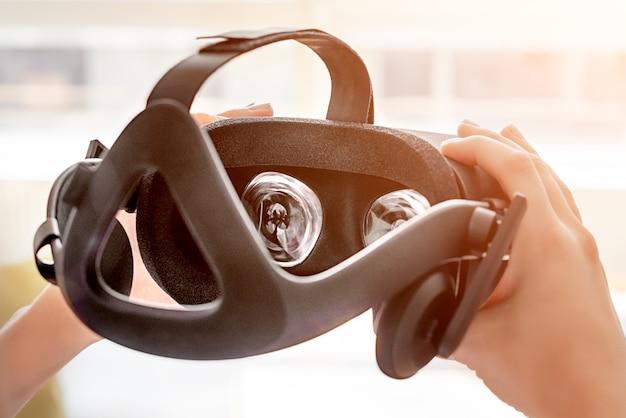 Mani che tengono il casco di realtà virtuale. concetto per la visualizzazione virtuale in futuro, gioco o video della tecnologia vr