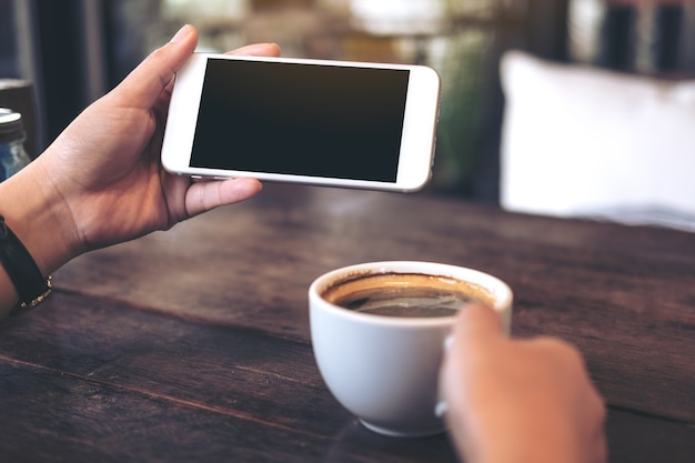 Mani che tengono il cellulare bianco con schermo nero vuoto per guardare e giocare