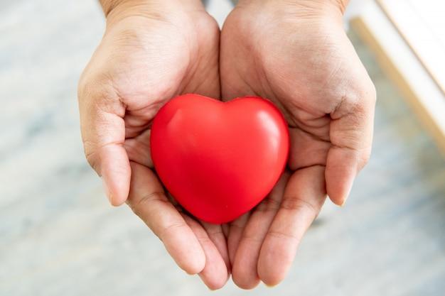 Mani che tengono il concetto di cuore, amore e cura di gomma rosso