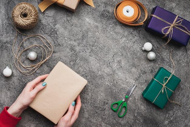 Mani che tengono il contenitore di regalo di natale con corda e le forbici