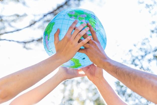Mani che tengono il globo gonfiabile