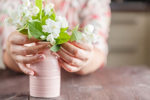Mani che tengono il mazzo di bellissimi fiori bianchi