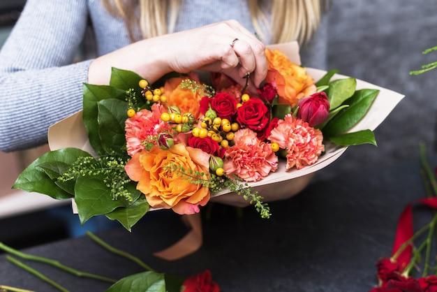 Mani che tengono il mazzo di vari fiori