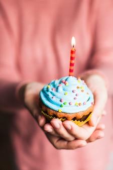 Mani che tengono il muffin di compleanno
