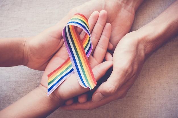 Mani che tengono il nastro arcobaleno di orgoglio gay per la consapevolezza lgbt