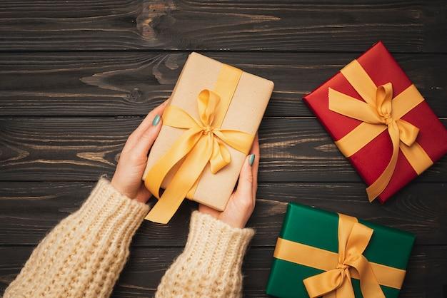 Mani che tengono il regalo di natale con il nastro dorato