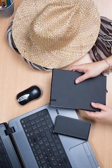 Mani che tengono il taccuino con laptop e cappello