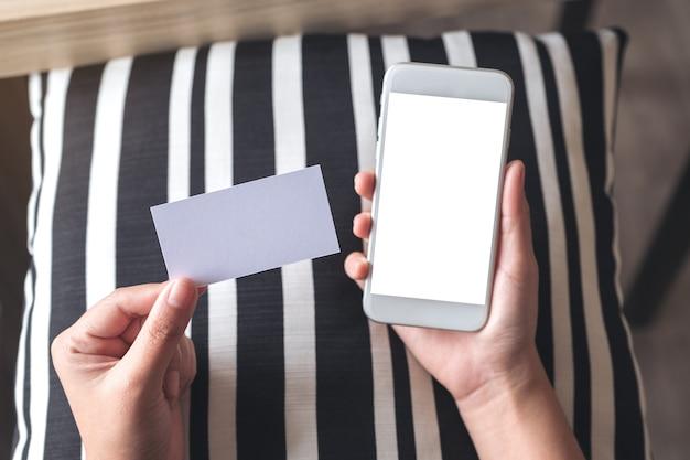 Mani che tengono il telefono cellulare bianco con schermo desktop vuoto e una carta bianca vuota