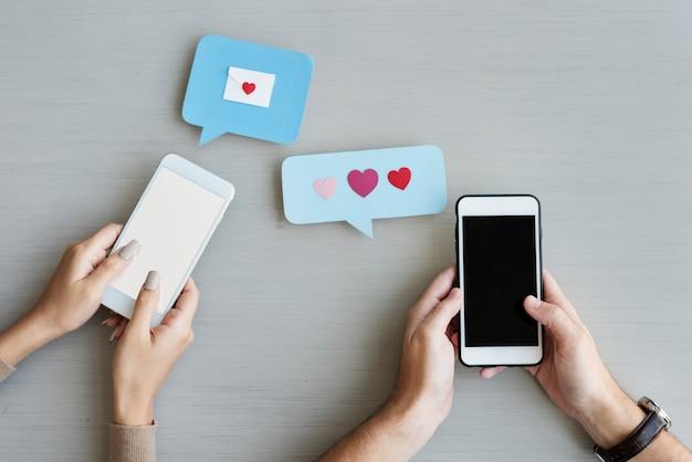 Mani che tengono il telefono cellulare che invia il fumetto del messaggio del cuore