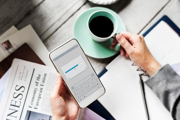 Mani che tengono il telefono cellulare di download con la bevanda della tazza di caffè
