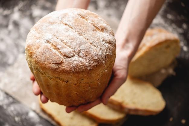Mani che tengono in casa pane fresco naturale con una crosta dorata su un vecchio legno. cuocere prodotti da forno