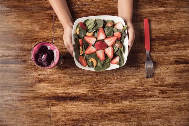Mani che tengono l'insalata di spinaci e fragola sul tavolo in legno e succo di barbabietola