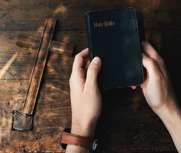 Mani che tengono la bibbia santa accanto alla croce di legno