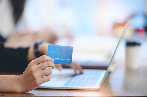 Mani che tengono la carta di credito e che per mezzo del computer portatile.