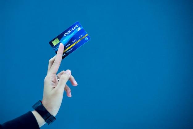 Mani che tengono la carta di credito in plastica per pagare.