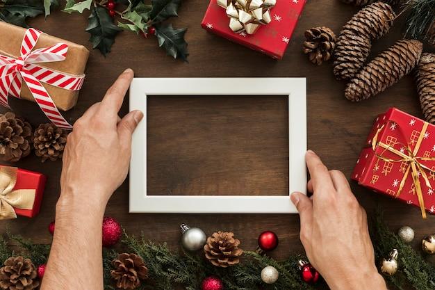 Mani che tengono la cornice tra le decorazioni natalizie