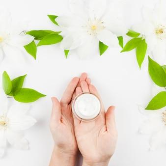 Mani che tengono la crema con fiori intorno