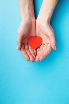 Mani che tengono la figura del cuore con lo spazio della copia