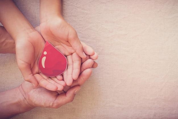Mani che tengono la goccia di sangue, concetto di giornata mondiale del donatore di sangue