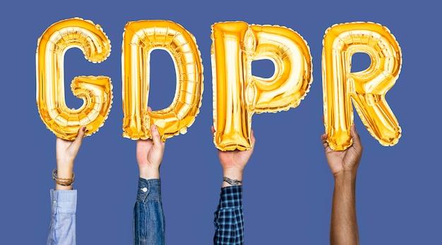 Mani che tengono la parola gdpr in lettere a palloncino