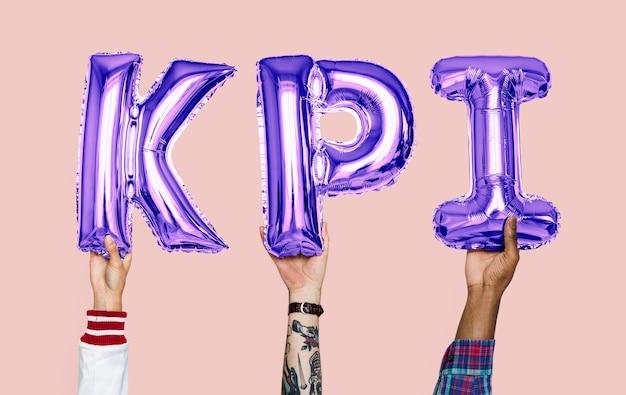 Mani che tengono la parola kpi in lettere a palloncino