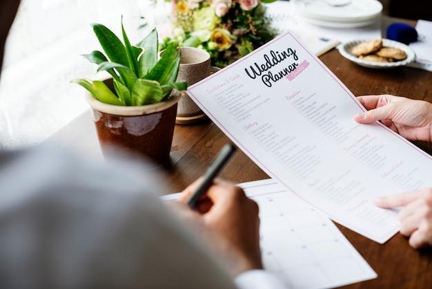 Mani che tengono la preparazione di informazioni della lista di controllo del pianificatore di nozze