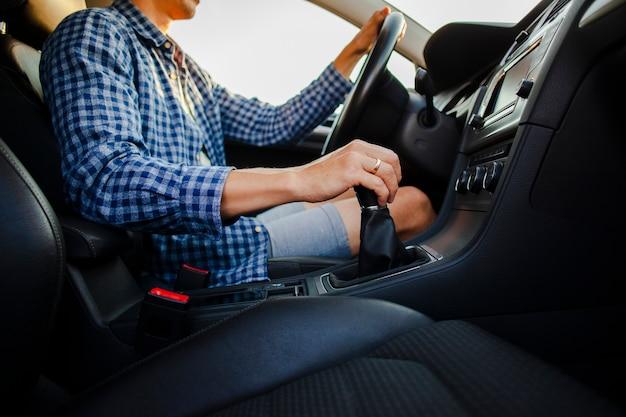 Mani che tengono la ruota di automobile e la leva del cambio
