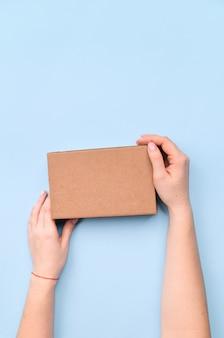 Mani che tengono la scatola del mestiere con come regalo per il natale, il nuovo anno o l'anniversario su fondo blu, vista superiore