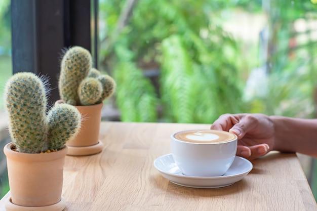 Mani che tengono la tazza di caffè bianco con il piattino sulla tavola di legno