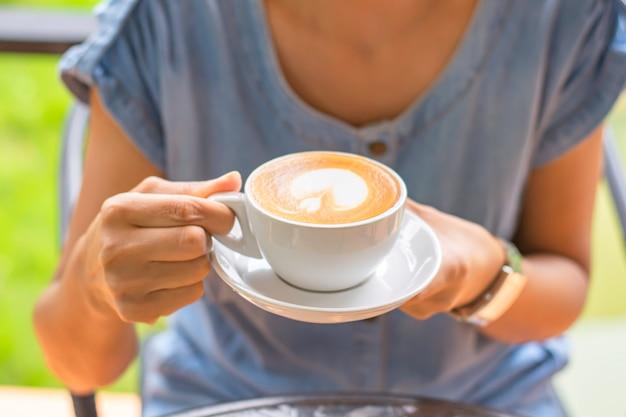 Mani che tengono la tazza di caffè bianco con piattino.