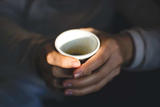 Mani che tengono la tazza di caffè espresso
